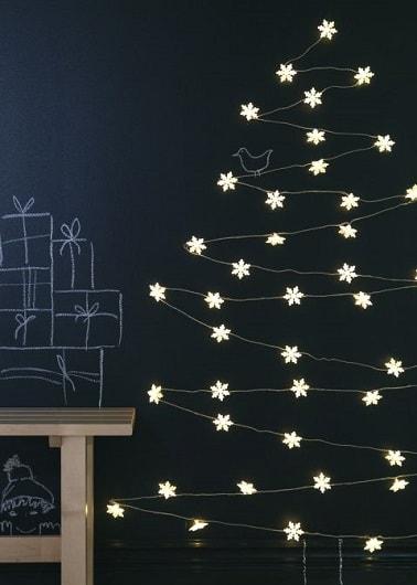 Ce sapin de Noël mise sur un look original grâce à une structure uniquement constituée d'une guirlande lumineuse Ikea. Accrochée au mur elle reprend la forme d'un vrai sapin.
