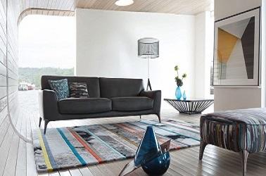 Dans ce salon au mobilier au look design, le canapé en cuir noir s'accorde avec le tapis en laine ethnique, la table basse design et le repose pieds recouvert d'un tissu imprimé reprenant les couleurs du tapis
