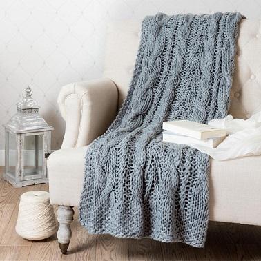 Un plaid grosses mailles de laine tricotées.