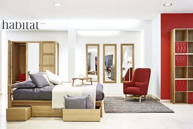 Un mobilier design fait la déco de cette chambre exposée dans le pop up store Habitat grâce à un lit avec rangements, un fauteuil rétro et un meuble avec étagères tendance.
