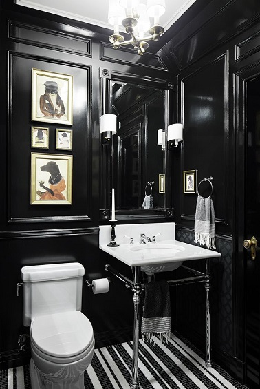 En total look noir, ce WC prend des allures de cabinet de curiosité avec des cadres originaux, des lumières stylées et un lave-mains au design authentique et aérien.