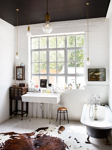 Peindre un plafond en noir dans une salle de bain blanche ça donne du caractère à la déco. Le plafond est assorti à la peinture noire de la baignoire îlot sur pieds.