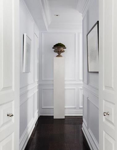Le total look blanc de cette déco couloir permet de rendre le passage d'origine étroite plus lumineux et aéré. Le sol foncé crée quant à lui un contraste déco chic.