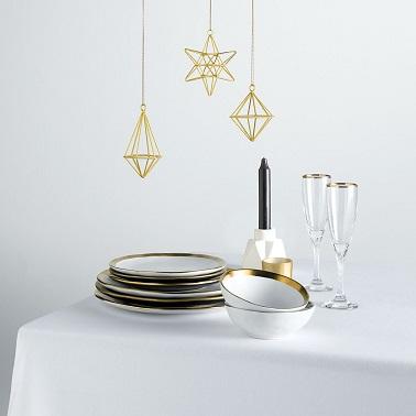 Comme les invités, la table de Noël adopte un look élégant et chic avec de la vaisselle assiettes et flûtes de champagne dorées au design signé Cristina Cordula pour Tati.