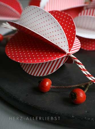 Une belle déco pour la table de Noël faite de boules rouge et blanche et de branches de houx
