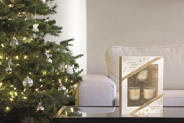 Un cadeau de Noël coffret avec des bougies décoratives et du thé gourmand.