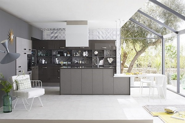 Une cuisine complètement ouverte et moderne avec îlot gris et meubles de cuisine anthracite. Déco papier peint vinyle carreaux de ciment.
