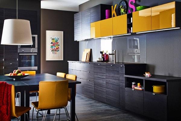 Une cuisine peps et moderne avec des meubles bois noirs et un élément linéaire à la façade jaune moutarde laquée.