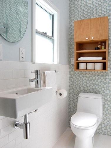 Ces petites toilettes sont relookées simplement avec une déco WC épurée et empreinte de lumière. Les murs sont habillés de faïence mosaïque en verre pour un style chic.