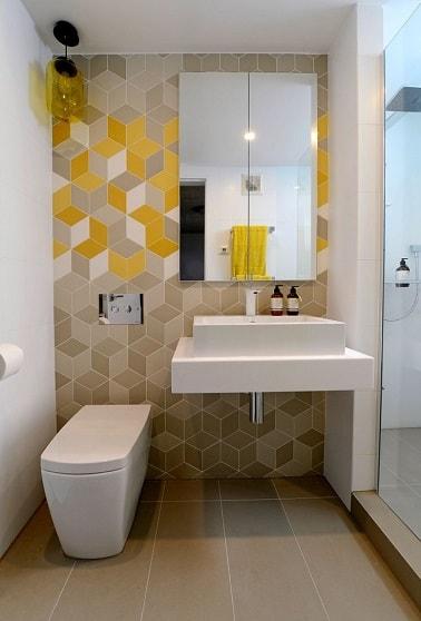 En quête d'originalité, le mur de ces cabinets met en lumière des carreaux de ciment cubiques. Beige avec des touches de jaune, cette déco WC stylée est pleine de peps.