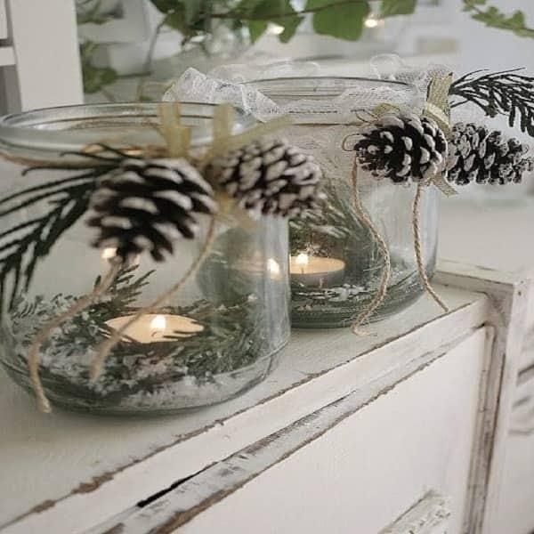 Des bocaux en verre décorés avec pommes de pin, ruban et épines de sapin comme photophores déco.