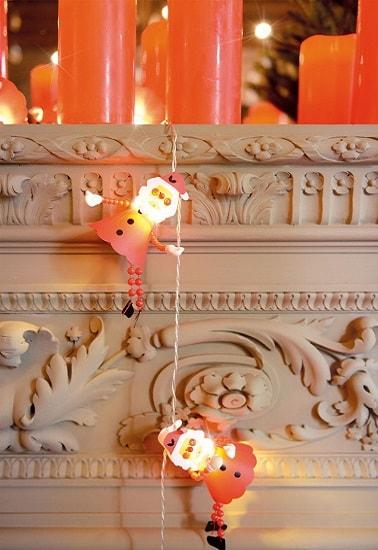 Cette guirlandes met en lumière des petits pères Noël qui semblent comme escalader la commode du salon. Une décoration de Noël enfantine et très mignonne pour la maison.