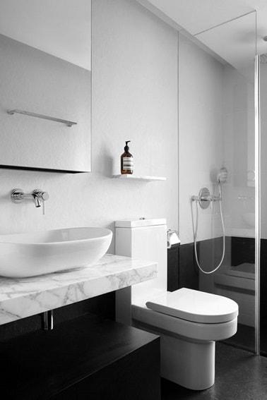 Adieu les cabinets datés et bonjour à cette déco WC chic en noir et blanc. Le soubassement peint en noir crée une unité avec le sol et contraste avec le haut de mur blanc.