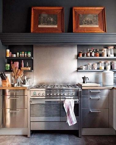 Une cuisine grise stylée avec une peinture gris anthracite sur la poutre et le haut du mur au dessus d'une crédence gris perle et des niches de rangement repeintes en gris souris, repris pour la couleur du carrelage sol.