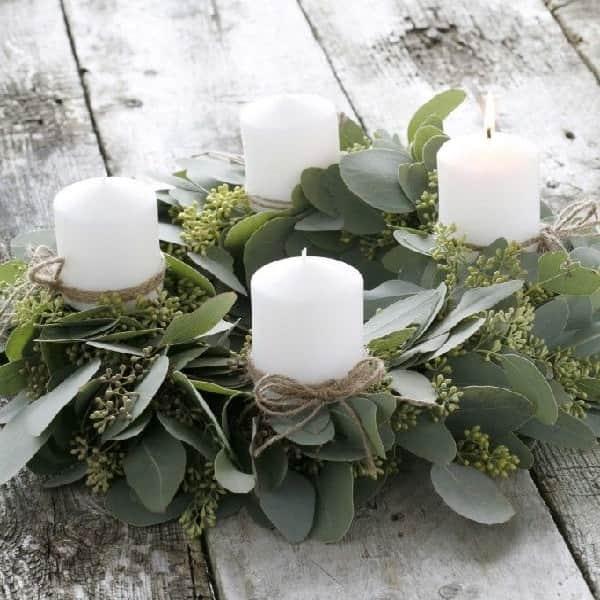 Une composition pour table de Noël avec une base végétale d'eucalyptus et des bougies pour illuminer Noël.