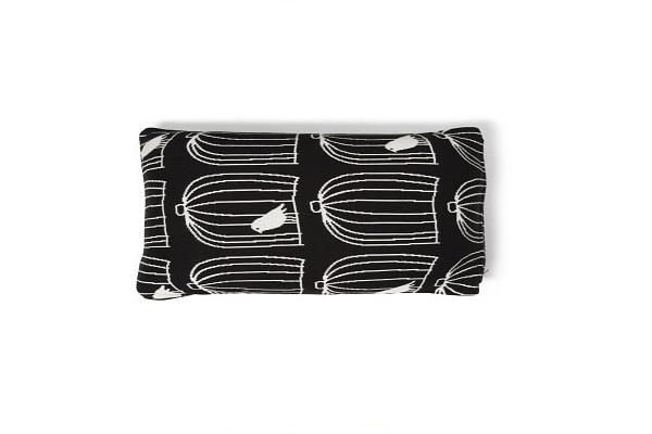 Un coussin à motifs cages d'oiseau noir et blanc pour Noël.