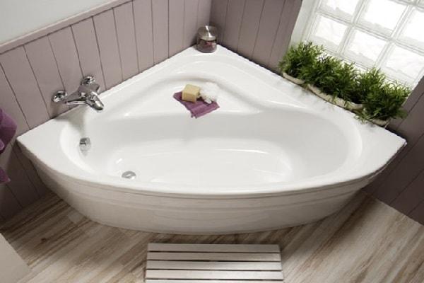 Une baignoire d'angle de forme amande avec rebord pour s'asseoir.