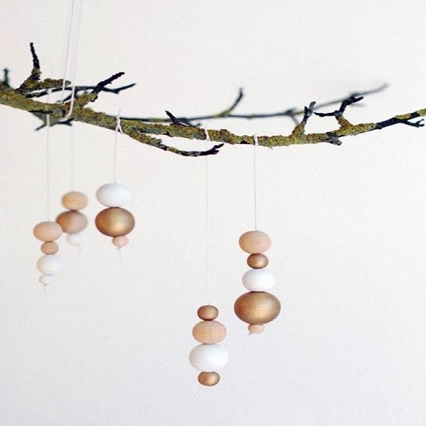 Des suspensions discrètes et raffinées faites avec des perles en bois, dorés et blanches.