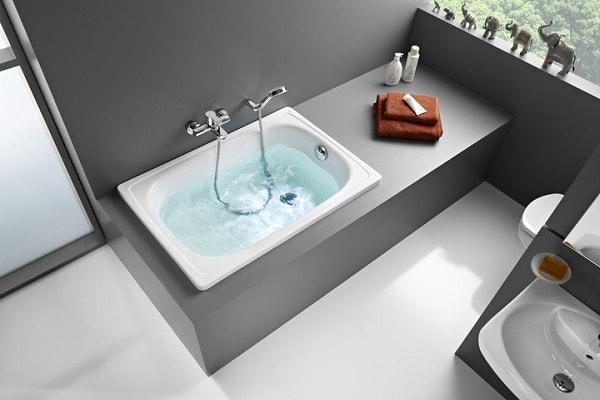 Robinetterie Salle De Bain Castorama : Une micro baignoire sabot dans une salle de bain grise.