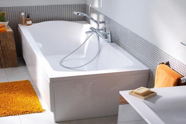 Une baignoire avec repose tête confort dans une salle d'eau minuscule.