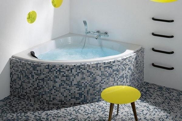 Une baignoire d'angle signée Jacob Delafon avec mosaïque faïence grise et bleue.