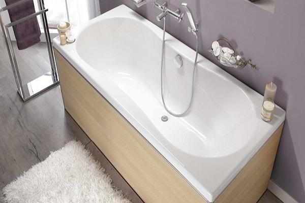 Une petite baignoire forme haricot et revêtement bois.
