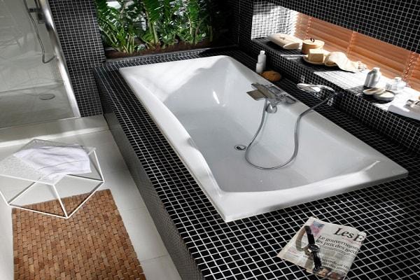 Une petite baignoire encastrée dans une salle de bain avec faïence noire.