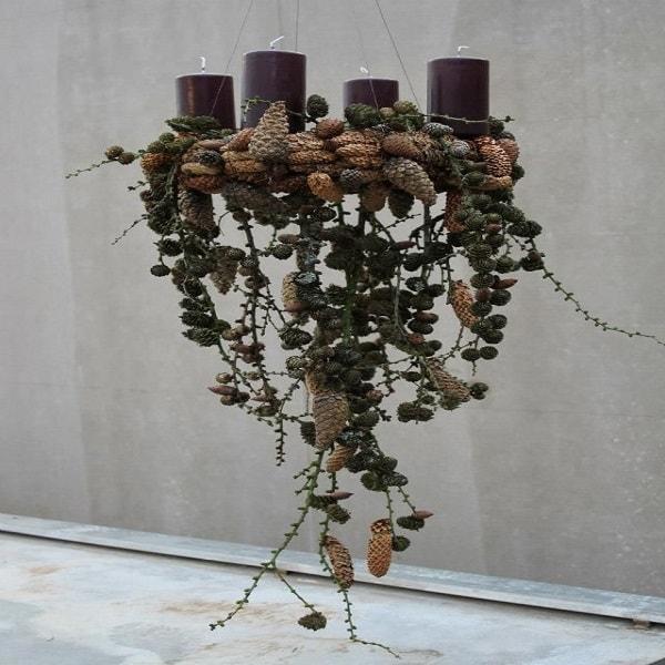 Une suspension qui met en valeur des bougies sur un lit d'éléments végétaux en tous genres pour une déco Noël contemporaine.