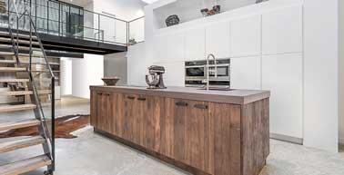 Ilot central en bois effet vieillit pour réchauffer cette cuisine ouverte d'inspiration loft contemporain. Un décor saisissant et unique réalisée par La Cuisine Française.