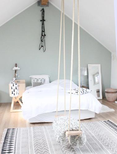 Une déco très originale dans cette chambre sous les combles avec une petite balançoire suspendue et un beau mur peint de couleur pastel pour une atmosphère délicate