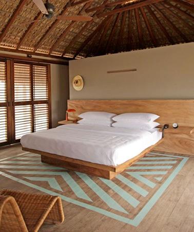 Une chambre sous combles ultra originale dans une villa mexicaine avec un beau tapis de peinture sur le parquet. Une déco idéale pour les vacances et pour se reposer dans une ambiance apaisante.