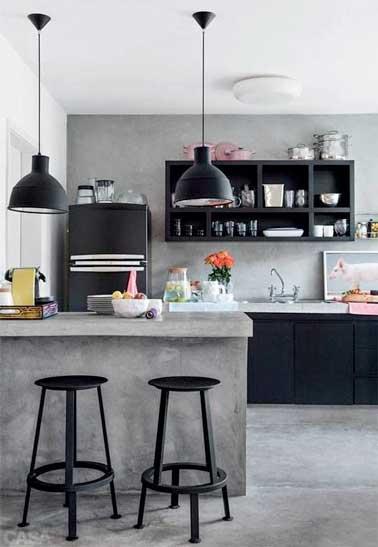 L'aspect doux du béton ciré indus sur le carrelage du sol et des murs de la cuisine ouverte s'harmonise avec l'électroménager et le mobilier en bois noir mat.