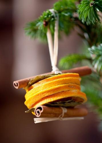 Osez l'originalité ! Confectionnez des boules de déco pour sapin hors du commun, fabriqués avec des tranches d'oranges et des bâtonnets de cannelle. Une déco aromatisée pour un sapin de Noël original