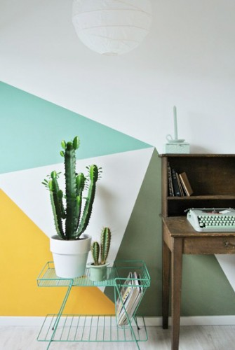Un bureau design et sophistiqué grâce à des triangles colorés peints sur un mur blanc. Une déco très tendance avec de la couleur et des formes géométriques jouant avec l'espace de la pièce.