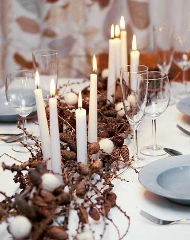 Spectaculaire ce centre de table ajoute une touche nordique sur la table de Noël. Déco bougies cierges blanches et vaisselle pastel sur une nappe blanche.