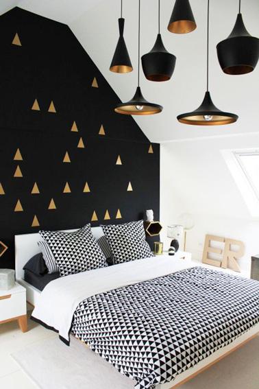 Du doré et du noir pour cette belle chambre d'amis aménagée sous les combles ! Une pièce à la déco originale avec ses lampes suspendues et ses triangles dorés.