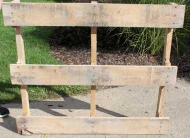 Pour démonter l'arrière de la palette en bois, on recommence la même opération en retirant les clous des planches de bois du haut vers le bas.