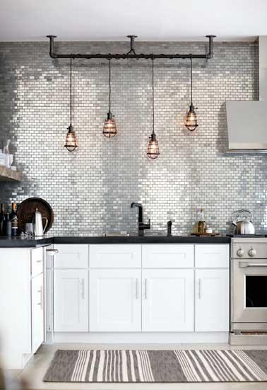 Déco de crédence en carreaux aluminium brillant pour relooker la cuisine grise. Plan de travail en pierre noir et électroménager en alu brossé donnent le ton.