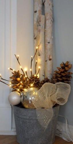 Un seau en étain se transforme rapidement en déco de Noël grâce à des boules colorées, des pommes de pins et des guirlandes lumineuses.