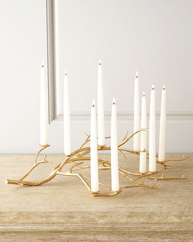 Sublimez votre déco de table de Noël en fabriquant un porte-bougies à l'aide d'une branche. Bombez-la de doré et fixez des bougies blanches avec des clous pour une table qui scintille de milles feux