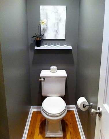 Ambiance déco rétro chic dans les wc en associant éléments décoratifs blanc et peinture gris. Bien vu l'étagère centrale design et les détails chromés.