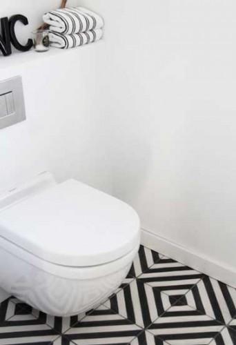 Belle harmonie déco dans ces toilettes blanche. Les carreaux de sol noirs et blancs aux motifs très forts s'imposent sous le bloc cuvette wc suspendu.