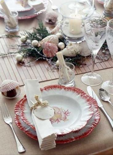 Table de Noël aux couleurs rouge et rose corail pour cette déco mer. Centre de table composé de coquillages décoratifs, de perles de mer et d'algues.