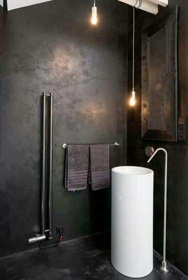Une douche italienne contemporaine en béton ciré noir. L'effet brut du revêtement béton est souligné par deux spots et les détails design de la colonne vasque