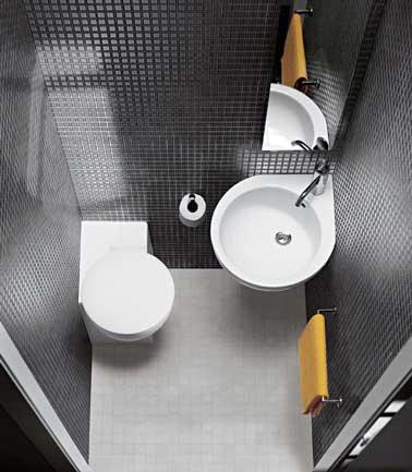 Tendance graphique en noir et blanc pour la déco de ces minis WC. Murs en carrelage noir pour la , lavabo en coin et miroir suspendu pour gagner de la place.