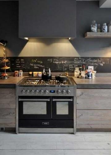 Déco industrielle pour la peinture gris anthracite de la cuisine ouverte. Crédence en pierre grise avec parquet et meubles de rangement en bois non traité.