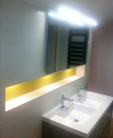 Le jaune peint en bande de couleur ajoute de la profondeur dans la salle de bain. Placée sous une source lumineuse, le ton jaune éclaire une petite pièce.