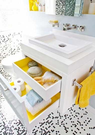 Le jaune une couleur joyeuse dans une petite salle de bain blanche. Elle investit l'intérieur des tiroirs du meuble blanc avec de l'adhésif, les objets déco