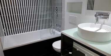 Noir et blanc : un tandem couleur chic dans une petite salle de bain. Le carrelage à rayures verticales posé sur la baignoire apporte de la hauteur à la pièce