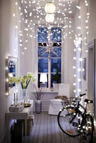 des guirlandes blanches pour cette décoration de Noël à fabriquer dans une petite entrée. Les guirlandes lumineuses placées un peu partout donnent le ton des fêtes !